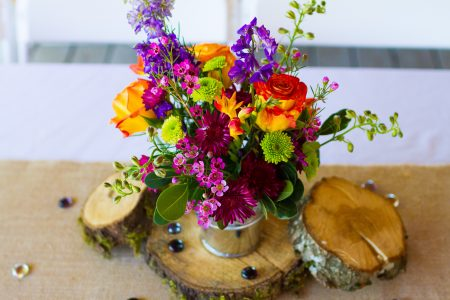 Wedding diy centerpieces on tables at a reception of orange and green flowers.